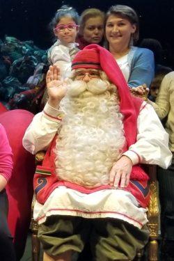 Mikołaj na fotelu. za nim stoi kobieta trzymająca dziewczynkę na rękach.