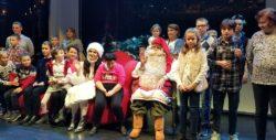 Zdjęcie grupowe. Mikołaj siedzący w fotelu wokół niego dużo dzieci.