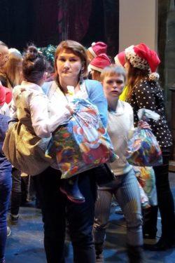 Na pierwszym planie kobieta trzymająca na rękach dziewczynkę. Dziewczynka trzyma kolorową torbę z prezentami. W tle inne osoby.