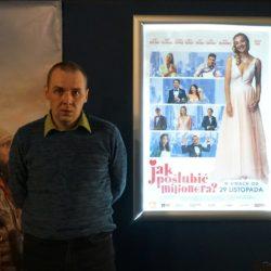 Jeden z mieszkańców obok plakatu z filmu: Jak poślubić milionera?