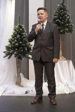 Pan Dyrektor mówi do trzymanego w prawym ręku mikrofonu na tle dwóch choinek.