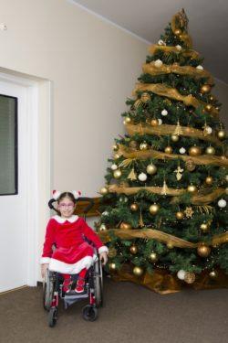 Uśmiechnięta dziewczynka w czerwonej sukience na wózku inwalidzkim na tle świątecznej choinki.