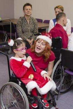 Na pierwszym planie dziewczynka na wózku inwalidzkim z mikrofonem w dłoni. Obok niej kobieta w czapce Mikołaja. W tle trzy inne osob.