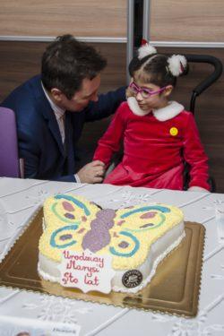Na pierwszym planie, na stole tort urodzinowy w kształcie motyla. W tle Dyrektor składający życzenia dziewczynce siedzącej na wózku inwalidzkim.
