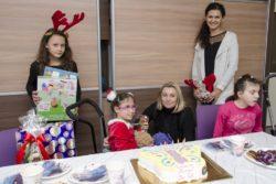 Zdjęcie grupowe. Za stołem na którym jest tort i inne słodycze siedzi śmiechnięta dziewczynka. Za nią stoją cztery osoby: dwie dziewczynki i dwie kobiety.