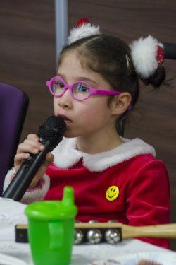 Za stołem siedzi dziewczynka trzymająca mikrofon na wysokości ust.