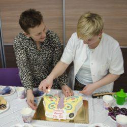 Dwie stojące przy stole kobiety. Na stole tort w kształcie motyla z zapalonymi świeczkami.