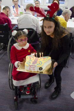 Dziewczynka na wózku inwalidzkim i dziewczynka trzymają razem tort w kształcie motyla z zapalonymi świeczkami.