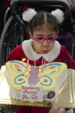 Dziewczynka na wózku inwalidzkim zdmuchuje zapalone świeczki na torcir w kształcie motyla.