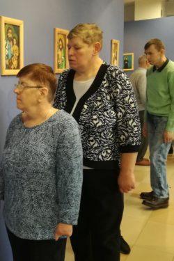 Dwie kobiety i jeden mężczyzna oglądają zawieszone na ścianach obrazy.