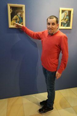 Chłopiec w czerwonym swetrze wskazuje dłonią na obraz zawieszony na ścianie.