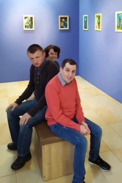 Trzy osoby siedzą na ławeczce ustawionej pośrodku zasli na której ścianach wiszą obrazy.
