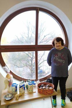 Kobieta stojąca na tle okrągłego okna. Po lewej stronie stolik z różnymi przedmiotami.