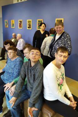 Grupa osób siedząca na ławce pośrodku sali. Na ścianach wiszą obrazy.