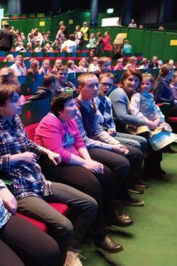 Zdjęcie ogólne. Siedzący w fotelach chłopcy i dziewczynki na widowni opery.