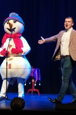 Na scenie dwie postaci. Osoba w stroju bałwanka i mężczyzna z rozportartymi ramionami.