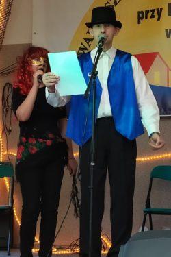 Mężczyzna w kolorowym stroju stoi przed mikrofonem i czyta tekst z kartki.