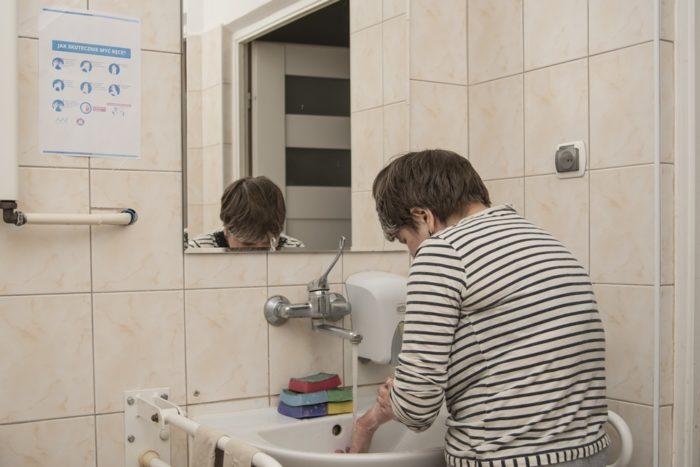 Kobieta myje ręce w łazience.