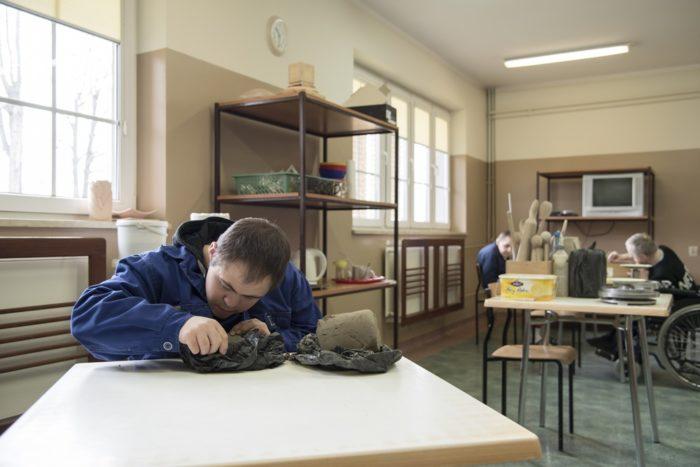 Chłopiec pracuje siedząc przy stoliku.