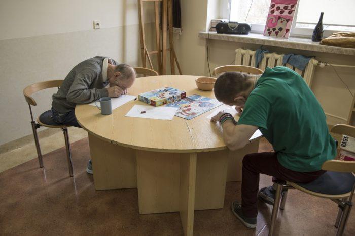 Dwóch mężczyzn rysuje siedząc przy okrągłym stoliku.