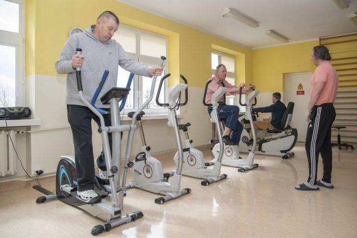 Czterch mężczyzn. Trzech ćwiczy na urządzeniach sportowych. Jeden stoi naprzeciw nich.