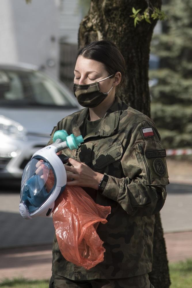 Kobieta w mundurze trzyma w rękach maskę ochronną.