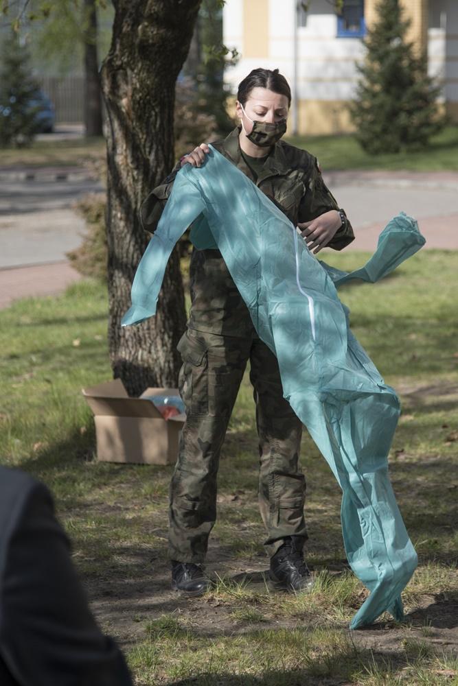 Kobieta w mundurze trzyma w rękach kombinezon ochronny.