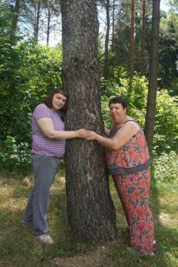 Dwie kobiety stoją przy drzewie.