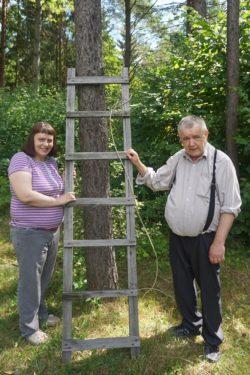 Kobieta i mężczyzna stoją przy drabinie opartej o drzewo.