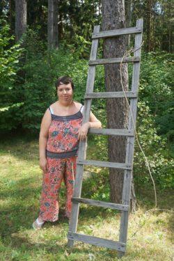 Kobieta stojąca przy drabinie opartej o drzewo.