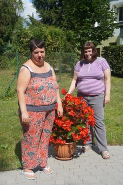 Dwie kobiety stoją przy donicy z czerwonymi kwiatami.