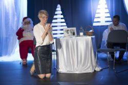 Na pierwszym planie klęczy kobieta obok udekorowanego stołu. Za nią w tle siedzi osoba w stroju Mikołaja i mężczyzna.