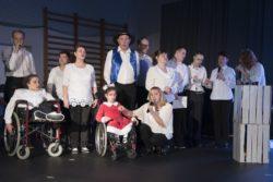 Na udekorowanej sali gimnastycznej stoi grupa odświętnie ubranych osób z mikrofonami w dłoniach, w tym dwie na wózkach inwalidzkich.
