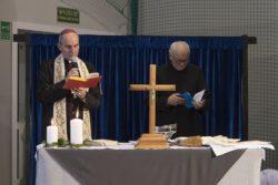 Udekorowany stół na którym stoi krzyż, dwie świece i nne przedmioty. Za stołem stoi dwóch duchownych z otwartymi księgami w rękach.