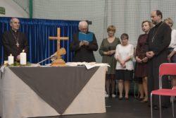 Na pierwszym planie stół na którym stoi krzyż i dwie świece. Za stołem biskup i ksiądż trzymający w rękach otwarte Pismo święte. Na prawo od stołu cztery kobiety i duchowny.