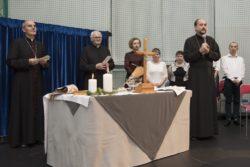 Na pierwszym planie stół przykryty obrusem. Na stole stoi krzyż, dwie świece i inne przedmioty. Za stołem trzech duchownych i cztery inne osoby. Jeden z duchownych trzyma w rękach mikrofon.