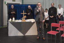 Mężczyzna w szarym grniturze mówi do mikrofonu. W tle stół przykryty obrósem z krzyżem i świecami. Za nim trzech duchownych i dwie inne osoby.