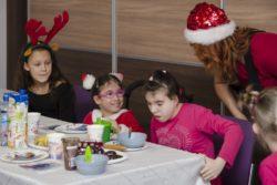 Cztery osoby: Trzy dziewczynki i kobieta w czapce Mikołaja, przy stole na którym znajdują się słodycze.