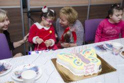 Na stole tort urodzinowy w kształcie motyla. Kobieta składający życzenia dziewczynce siedzącej na wózku inwalidzkim. Po bokach dwie inne osoby.