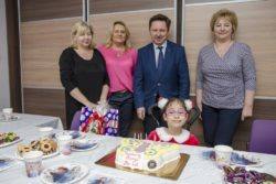 Zdjęcie grupowe. Za stołem na którym jest tort i inne słodycze siedzi śmiechnięta dziewczynka. Za nią stoją cztery osoby: Dyrektor i trzy kobiety.