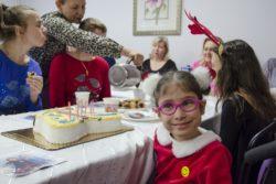 Na pierwszym planie uśmiechnięta dziewczynka. W tle stół z tortem i siedzącymi przy nim osobami.