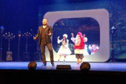 Mężczyzna na scenie. Za nim w tle Mikołaj i kobieta w białej eleganckiej sukni.