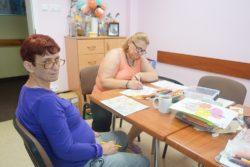 Dwie kobiety siedzą przy stole i rysują