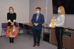 Trzy osoby stoją w pomieszczeniu. Dwie kobiety i mężczyzna. Kobieta po lewej stronie trzyma w rękach torbę na prezenty. Kobieta po prawej stronie trzyma otrzymany upominek.