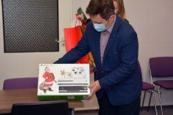 Mężczyzna prezentuje otrzymany prezent, konsolę Xbox.
