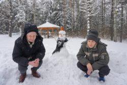 Dwaj przykucnięci mężczyźni na śniegu. Pomiędzy nimi ulepiony bałwan. W tle las i altana.