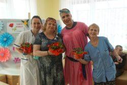 Trzy panie trzymające w dłoniach kolorowe kwiaty i przebrany za kobietę mężczyzna.