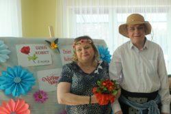 Kobieta i przebrany za kobietę mężczyzna stoją przy udekorowanej kwiatami z bibuły tablicy, z napisem: Dzień Kobiet 8 Marca.