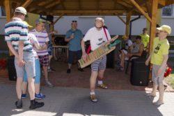 Tańczące osoby i mężczyzna z instrumentem muzycznym.