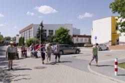 Idąca drogą pomiędzy budynkami grupa osób.
